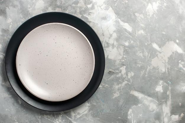 Вид сверху круглой пустой тарелки черного цвета с белой тарелкой на серой поверхности