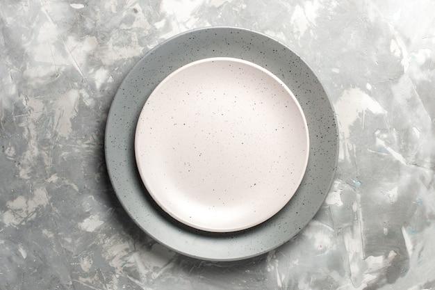 灰色の表面に白いプレートで着色された灰色の丸い空のプレートの上面図