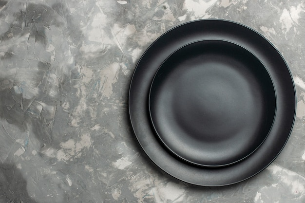 Вид сверху круглых пустых тарелок черного цвета на серой поверхности