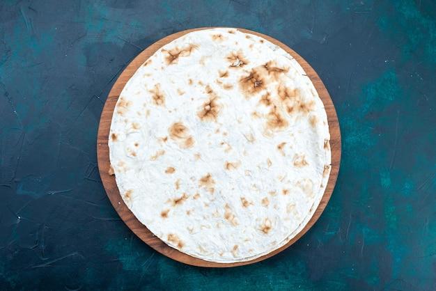 Вид сверху на круглый простой лаваш, испеченный как тесто на темно-синей поверхности