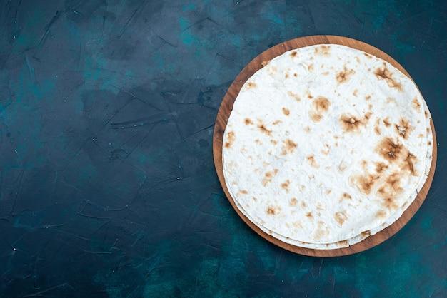 진한 파란색 표면에 반죽처럼 둥근 일반 피타 구운 빵의 평면도