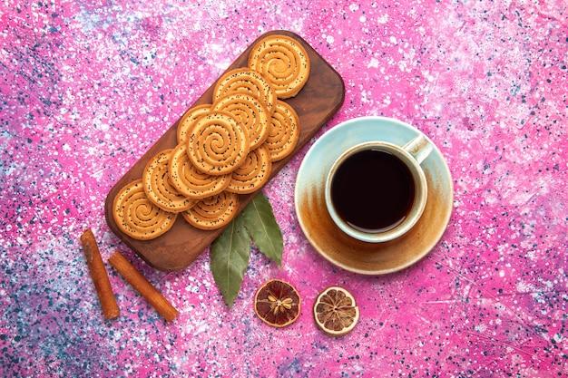 ピンクの表面にお茶とシナモンが並ぶ丸い甘いクッキーの上面図