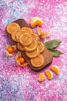 Вид сверху круглого сладкого печенья с мандаринами на розовой поверхности
