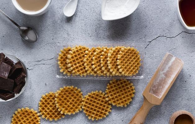 Вид сверху круглых вафель с кусочками шоколада и деревянной ложкой