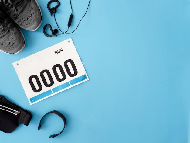 ランニングシューズ、よだれかけ番号、青の背景にランニングアクセサリーと実行中のイベントコンセプトのトップビュー。