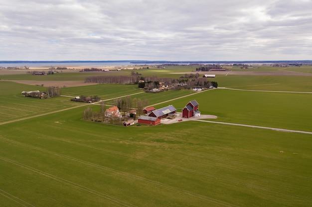 Взгляд сверху сельского ландшафта на солнечный весенний день. ферма с солнечной фотоэлектрической панелью на деревянном здании, сарае или крыше дома. зеленое поле копирования пространство. производство возобновляемой энергии.