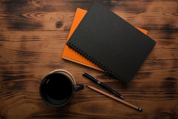 ノートペン、鉛筆、コーヒーカップと素朴な木製テーブルの上面図