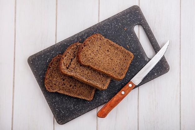 Вид сверху на ломтики ржаного хлеба и нож на разделочной доске на деревянном фоне