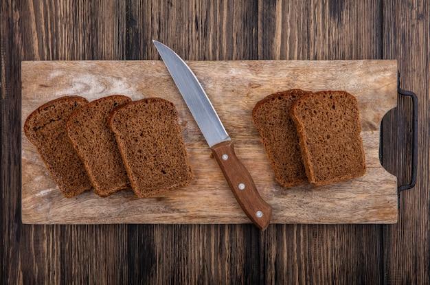 木製の背景にまな板の上のライ麦パンのスライスとナイフのトップビュー