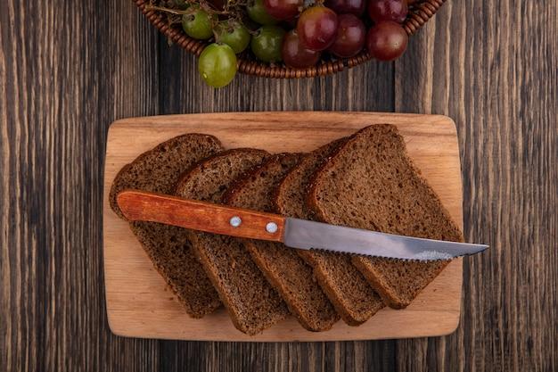 木製の背景にブドウのバスケットとまな板の上のライ麦パンのスライスとナイフのトップビュー