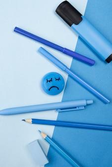 Вид сверху грустного лица с карандашами и маркером на синий понедельник