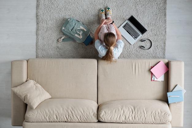 Вид сверху грустной студентки-подростка, обнимающей ее ноги, сидя на полу у дивана во время учебы дома во время карантина