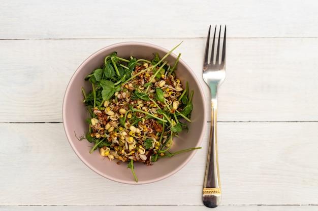 Вид сверху на салат из гороха с зелеными ростками и проросшей фасолью в миске