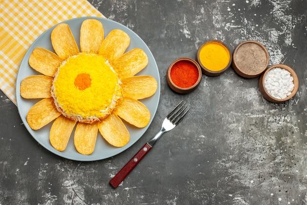 左側にサラダの上面図、その下に黄色のナプキン、ハーブとフォークが濃い灰色のテーブルにあります