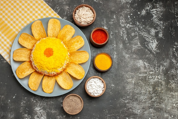 어두운 회색 테이블에 측면에 허브와 함께 그 아래 노란색 냅킨과 왼쪽에 샐러드의 상위 뷰