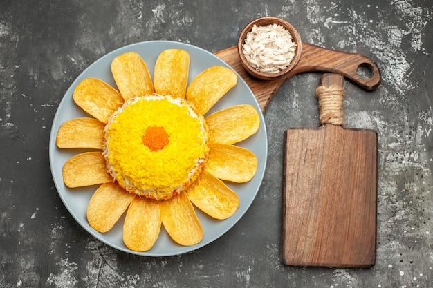접시에 샐러드의 상위 뷰는 어두운 회색 테이블에 측면에 치즈 그릇과 도마와 함께 서