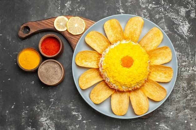濃い灰色のテーブルの側面にレモンとハーブとプレートスタンドのサラダの上面図