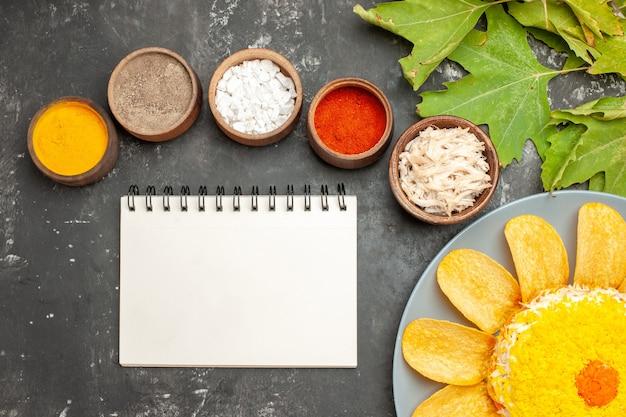 ハーブのメモ帳と濃い灰色の背景の側の葉と下側のサラダの上面図