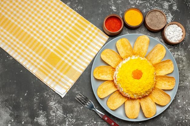 ハーブフォークと濃い灰色の背景の側面に黄色のナプキンと左側のサラダの上面図