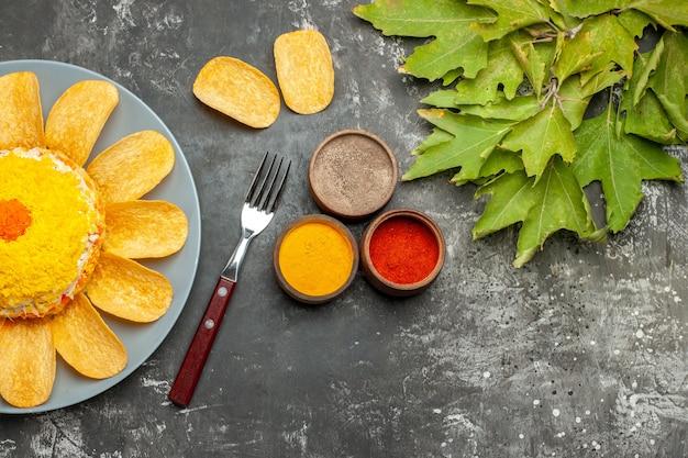 ハーブフォークチップと濃い灰色のテーブルの側面に葉を持つ左側のサラダの上面図