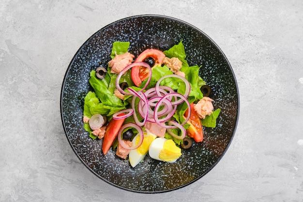 Вид сверху салат с листьями салата, лососем, помидорами, вареным яйцом и луком с оливками