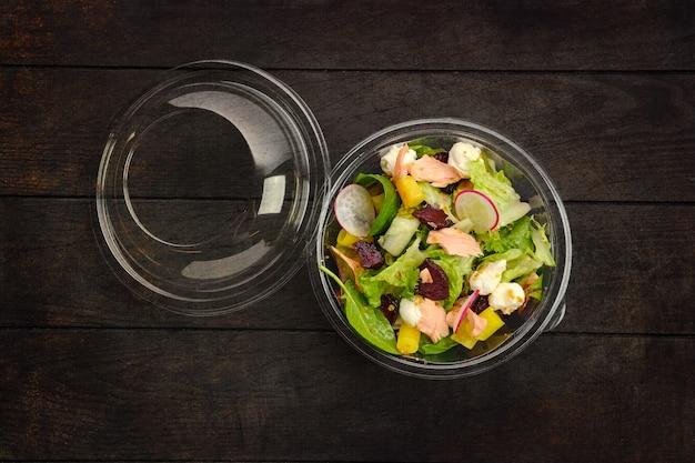 Вид сверху на салат с лососем, редисом, цукини и свеклой в упаковке на вынос