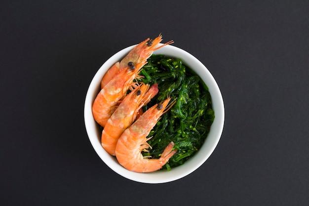 Вид сверху салат с водорослями и красными креветками в белой миске на черном фоне. крупным планом.