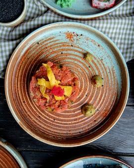 Вид сверху салат из лосося с авокадо и соусом васаби на тарелке на клетчатой ткани