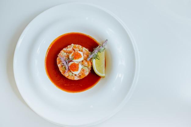 Вид сверху тартар из лосося с томатным гаспачо и сельдереем на белой тарелке. копировать пространство