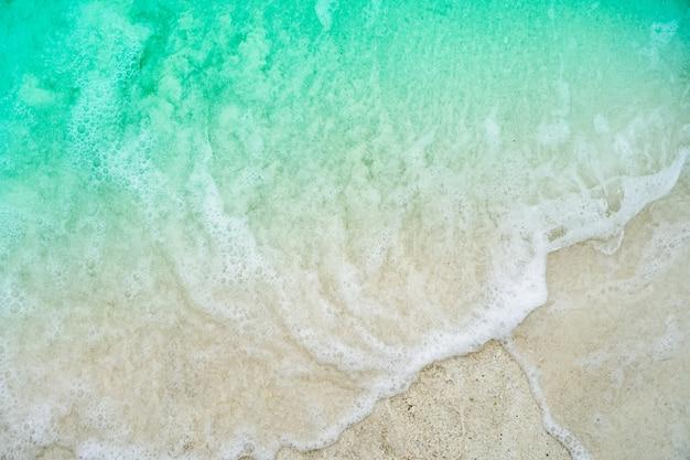 Взгляд сверху пляжа песка и воды чистых и белого песка в лете с светом солнца - предпосылкой голубого неба и bokeh.