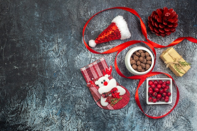 暗い表面の左側にあるサンタクロースの帽子とコーネルチョコレートの新年の靴下の赤い針葉樹の円錐形の上面図