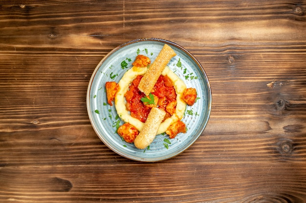 茶色の木製テーブルにマッシュポテトとスライスしたパンとソース肉の上面図