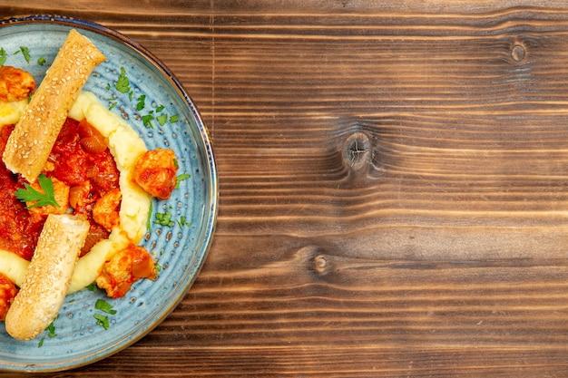 갈색 나무 테이블에 mushed 감자와 슬라이스 롤빵과 소스 고기의 상위 뷰