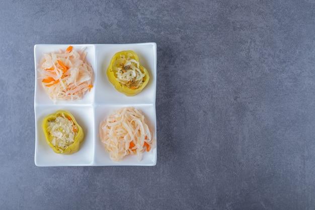 흰 접시에 소금에 절인 양배추와 녹색 채워진 고추의 최고 전망.