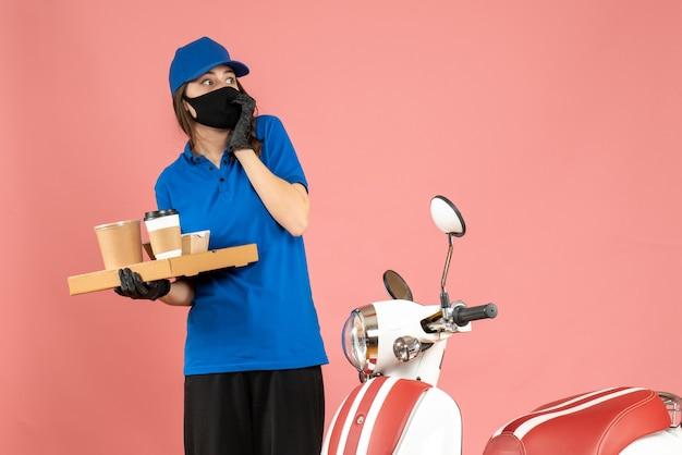 パステル ピーチ色の背景にコーヒーの小さなケーキを保持しているオートバイの隣に立っている医療マスク手袋を着て怖い宅配便の女の子のトップ ビュー
