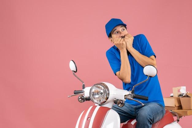 パステル調の桃の背景に注文を配達するスクーターに座っている帽子をかぶった怖い配達人のトップビュー