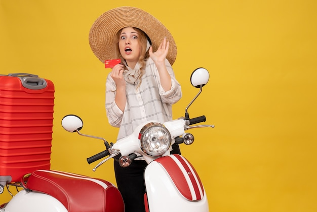 오토바이에 앉아 은행 카드를 들고 그녀의 수하물을 수집하는 모자를 쓰고 무서워 젊은 여자의 상위 뷰
