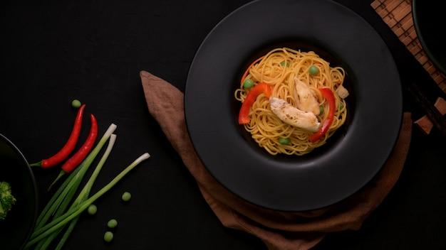 黒皿に野菜と鶏肉のシェズワン麺のトップビュー
