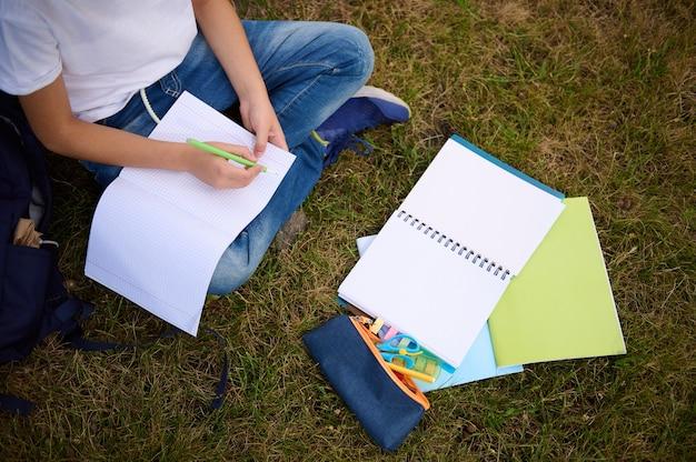 ワークブックの空の空白のシートに書いている学童の手の上面図。公園で宿題をしている小学生のトリミング画像。草の上に横たわる学用品