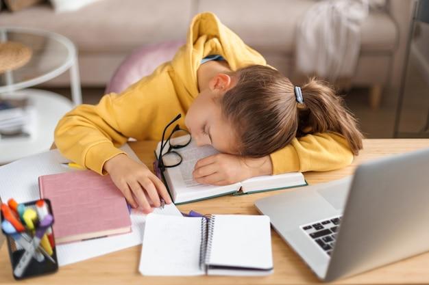 Вид сверху школьницы, спящей на открытой книге, делая домашнее задание с ноутбуком