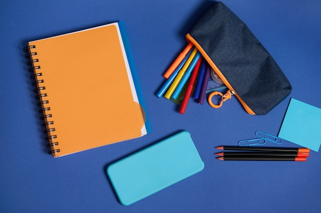 Вид сверху школьных канцелярских товаров и экрана смартфона, лежа на синем фоне. плоская композиция канцелярских принадлежностей двух контрастных цветов, синего и оранжевого, с копией пространства