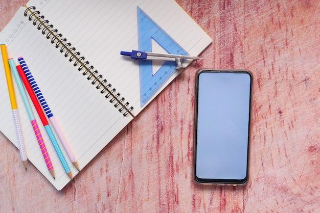 コピースペースとテーブルの上の学校のサプライヤーとスマートフォンの上面図。