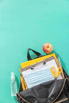 Вид сверху школьных принадлежностей с копией пространства и сумка для книг