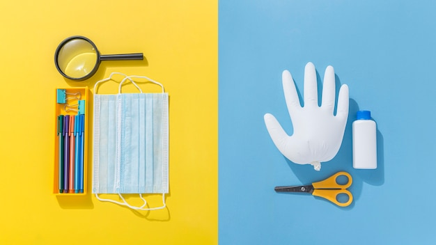 Вид сверху школьных принадлежностей с медицинской маской и ножницами