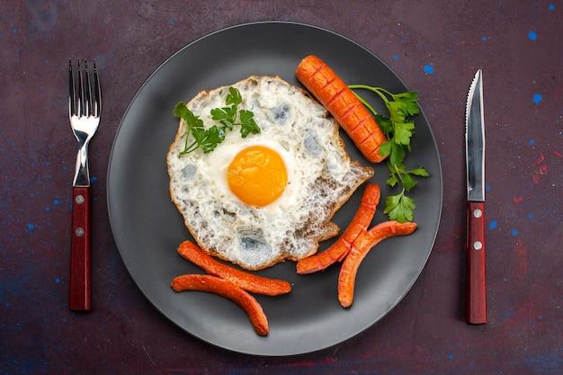 어두운 표면에 접시 안에 채소와 소시지와 스크램블 에그의 상위 뷰