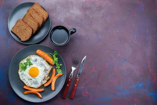Вид сверху на яичницу с сосисками и зеленью, хлеб, хлеб, чай на темной поверхности