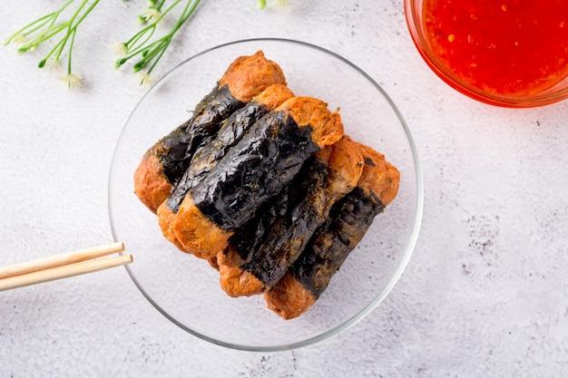 해초 치킨 롤의 상단 보기는 젓가락과 달콤한 칠리 소스가 있는 유리 접시에 쌓여 있습니다.