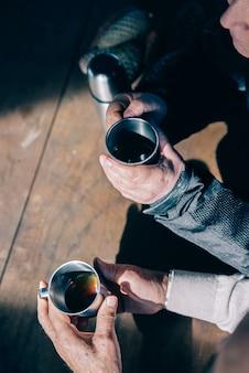 Вид сверху на руки пожилой пары, держащей металлические чашки и пьющих кофе за деревянным столом