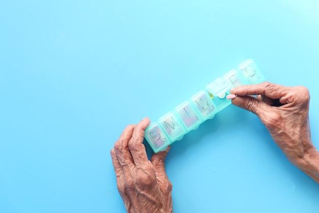 Вид сверху пожилых женщин, принимающих таблетку из коробки для таблеток