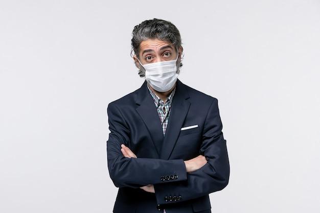 白い背景の上のマスクを身に着けているスーツの真面目な若い男の上面図